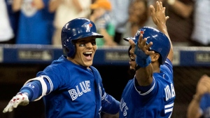 Toronto Blue Jays' Ryan Goins, left, celebrates his grand-slam against the New York Yankees with Richard Urena in the sixth inning in their American League MLB baseball game in Toronto on Friday, September 22, 2017. THE CANADIAN PRESS/Fred Thornhill