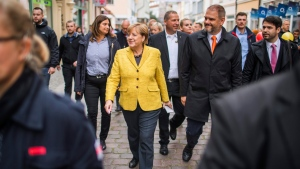 German chancellor Angela Merkel, front left, is accompanied by Stralsund mayor Alexander Badrow, third right, as she takes a stroll through the old town of Stralsund, at the Baltic Sea, Germany, Saturday, Sept. 23, 2017 one day ahead of Germany's general elections on Sunday. (Jens Buettner/dpa via AP)