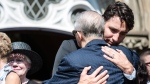 Prime Minister Justin Trudeau hugs the father of former Liberal MP Arnold Chan during his funeral service in Toronto on Saturday, September 23, 2017. THE CANADIAN PRESS/Christopher Katsarov