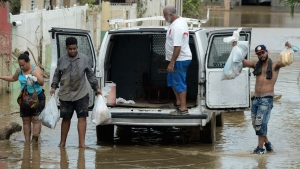 Residents manage provisions after the passing of Hurricane Maria, in Toa Baja, Puerto Rico, Friday, September 22, 2017. Because of the heavy rains brought by Maria, thousands of people were evacuated from Toa Baja after the municipal government opened the gates of the Rio La Plata Dam. (AP Photo/Carlos Giusti)