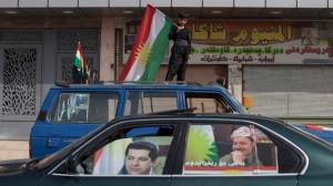 A boy carries a Kurdish flag on top of a car as a car with the faces of Kurdish president Masoud Barzani and his son Masrour on the windows passes by in the disputed city of Kirkuk, Monday, Sept. 25, 2017. Iraq's Kurdish region vote in a referendum on whether to secede from Iraq. (AP Photo/Bram Janssen)