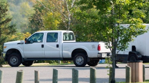 A truck and trailer where a man and young boy went missing is shown next to a park in Lachute, Que., Friday, September 15 , 2017. Quebec provincial police confirm a woman found dead in suburban Montreal is the mother of a six-year-old boy who is the subject of an Amber Alert. THE CANADIAN PRESS/Graham Hughes