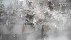 Workers shovel debris off the top of a building that collapsed in last week's 7.1 magnitude earthquake, at the corner of Gabriel Mancera and Escocia streets in the Del Valle neighborhood of Mexico City, Monday, Sept. 25, 2017. Search teams were still digging through dangerous piles of rubble Monday, hoping against the odds to find survivors after the Sept. 19 quake. (AP Photo/Rebecca Blackwell)