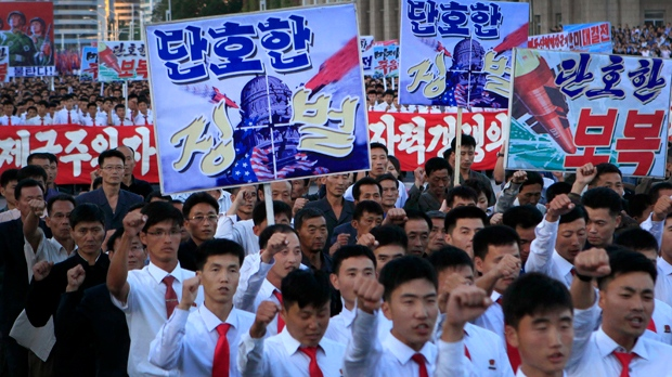 """North Koreans gather at Kim Il Sung Square to attend a mass rally against America on Saturday, Sept. 23, 2017, in Pyongyang, North Korea, a day after the country's leader issued a rare statement attacking Donald Trump. The sign on the left foreground reads """"decisive punishment"""" while the sign on the right reads """"decisive revenge."""" (AP Photo/Jon Chol Jin)"""