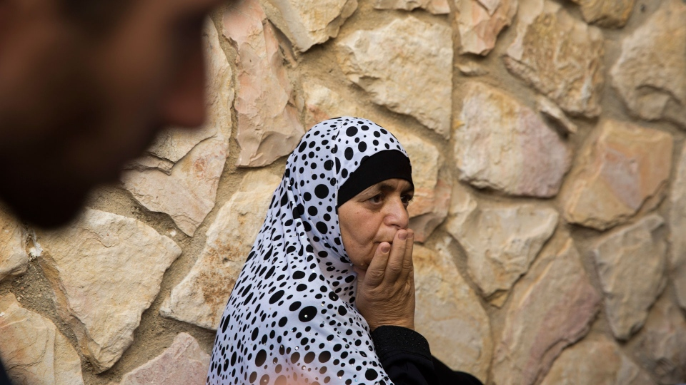 Israeli Arab woman mourns as the coffin of security guard Yussef Utman passes during his funeral in the village of Abu Gosh near Jerusalem, Israel, Tuesday, Sept. 26, 2017. Utman was killed with another security guard and a border police officer after a Palestinian attacker opened fire at an entrance to a Jewish settlement earlier. (AP Photo/Ariel Schalit)