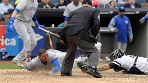 Toronto Blue Jays' Ezequiel Carrera, left, scores on a sacrifice fly by Josh Donaldson as New York Yankees catcher Gary Sanchez loses the ball during the eighth inning of a baseball game Saturday, Sept.30, 2017, at Yankee Stadium in New York. (AP Photo/Bill Kostroun)