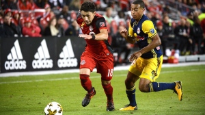 Toronto FC's Marky Delgado, left, chases the ball ahead of New York Red Bulls' Tyler Adams during second half MLS soccer action Saturday September 30, 2017 in Toronto. THE CANADIAN PRESS/Jon Blacker