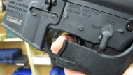 """In this Feb. 1, 2013, file photo, an employee of North Raleigh Guns demonstrates how a """"bump"""" stock works at the Raleigh, N.C., shop. The gunman who unleashed hundreds of rounds of gunfire on a crowd of concertgoers in Las Vegas on Monday, Oct. 2, 2017, attached what is called a """"bump-stock"""" to two of his weapons, in effect converting semiautomatic firearms into fully automatic ones. (AP Photo/Allen Breed, File)"""