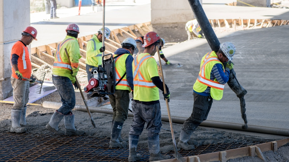 Workers lay concrete for a new skating trail underneath a section of the Gardiner Expressway. (Sean Galbraith)