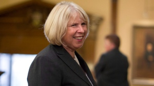 Deb Matthews makes her way through the legislature as she prepares to be sworn in as president of the Treasury Board at Queens Park in Toronto on Tuesday June 24, 2014. THE CANADIAN PRESS/Chris Young