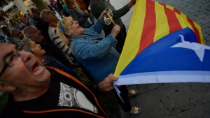 "Pro-independence supporters shout slogans in front of the Popular Party headquarters as a woman holds up ""esteleda"" or pro-independence flag, in support of the Catalonia's secession, in Pamplona, northern Spain, Friday, Oct. 6, 2017. (AP Photo/Alvaro Barrientos)"