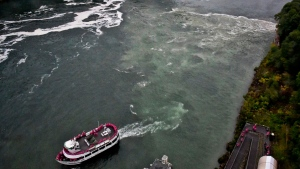 A tour boat travels a long the Niagara River where a series of overflow discharge from a treatment plant have drawn widespread attention, Monday, Oct. 9, 2017, in New York. (James Neiss/The Niagara Gazette via AP)