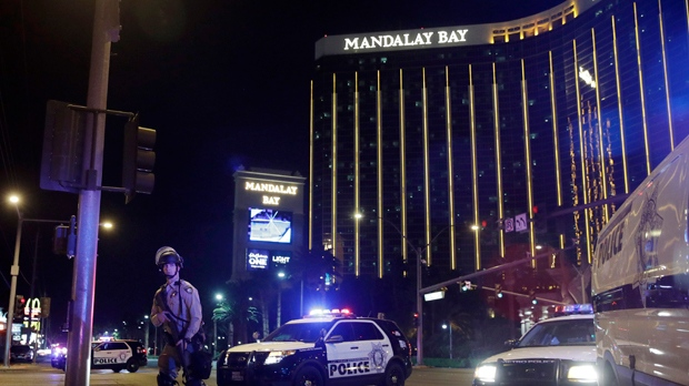 FILE - In this Sunday, Oct. 1, 2017 file photo, police officers stand along the Las Vegas Strip near the Mandalay Bay resort and casino during a shooting at a country music festival, in Las Vegas. Police initially said Stephen Paddock stopped firing on the music festival concert crowd below to shoot through his door and wound a Mandalay Bay security guard who was outside. On Monday, Oct. 9, 2017, they said the guard actually was wounded before Paddock started the massacre. (AP Photo/John Locher, File)