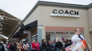 FILE - In this Friday, Nov. 27, 2015, file photo, shoppers wait in line outside a Coach factory outlet store at the Cincinnati Premium Outlets, in Monroe, Ohio.  (AP Photo/John Minchillo, File)