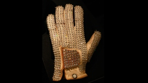 In this Nov. 21, 2009, file photo, Michael Jackson's glove from his 1983 performance of Billie Jean at the Motown 25 television special where he performed the Moonwalk for the first time is on display at the Hard Rock Cafe in New York's Times Square. Julien's Auctions announced on Oct. 13, 2017, that the glove is one of several  Jackson memorabilia items set to go up for bid on Nov. 4. (AP Photo/Mary Altaffer, File)