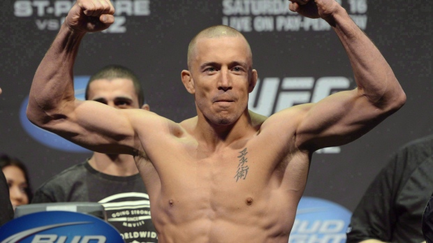 Fighter Georges St-Pierre flexes during the weight-in for UFC 158 in Montreal on March 15, 2013. Former welterweight champion St-Pierre says he will be bigger and better in his November comeback fight against middleweight title-holder Michael Bisping. THE CANADIAN PRESS/Ryan Remiorz