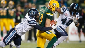 Toronto Argonauts' Jermaine Gabriel, left, and Bear Woods, right, tackle Edmonton Eskimos' Brandon Zylstra during second half CFL football action in Edmonton, Saturday, Oct. 14, 2017. THE CANADIAN PRESS/Jeff McIntosh
