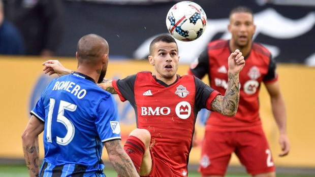 Toronto FC's Sebastian Giovinco (centre) plays the ball as Montreal Impact midfielder Andres Romero (15) looks on during MLS soccer action in Toronto on Sunday, Oct.15, 2017. THE CANADIAN PRESS/Frank Gunn