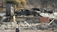 Two cars are among the remains Monday, Oct. 16, 2017, at the house where Sara and Charles Rippey died a week ago in a fast-moving wildfire in Napa, Calif. The couple, 98- and 100-years-old, respectively, had been married over 75 years. With the winds dying down, fire crews gained ground as they battled wildfires that have devastated California wine country and other parts of the state over the past week, and thousands of people got the all-clear to return home. (AP Photo/Eric Risberg)