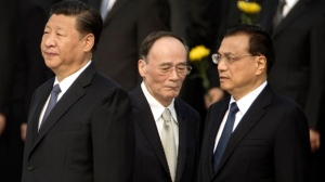FILE - In this Sept. 30, 2017 file photo, Chinese President Xi Jinping, left, Politburo Standing Committee member Wang Qishan, center, and Chinese Premier Li Keqiang attend a ceremony marking Martyrs' Day at Tiananmen Square in Beijing. Having bested his rivals, Chinese President Xi is primed to consolidate his already considerable power as the country's ruling Communist Party begins its twice-a-decade national congress on Wednesday, Oct. 18. (AP Photo/Mark Schiefelbein, File)