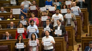 "Lawmakers hold up posters reading: ""Free Jordi Sanchez and Jordi Cuixart,"" leaders of the Catalan grassroots organizations Catalan National Assembly and Omnium Cultural, during a parliamentary session at the Spanish parliament in Madrid, Wednesday, Oct. 18, 2017. About 50 Spanish and Catalan party lawmakers held up posters in the parliament demanding the release of two pro-Catalonia independence movement leaders, describing them as political prisoners. (AP Photo/Francisco Seco)"