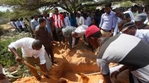 Somalis bury a body of a victim who died in Saturday's truck blast, in Mogadishu's Medina hospital graveyard in Mogadishu, Somalia, Tuesday, Oct, 17, 2017. A United States military plane has landed in Somalia's capital with medical and humanitarian aid supplies after Saturday's massive truck bombing killed more than 300 people. (AP Photo/Farah Abdi Warsameh)