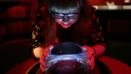"""A member of British Library staff poses with a crystal ball for a picture at the """"Harry Potter - A History of Magic"""" exhibition at the British Library, in London, Wednesday Oct. 18, 2017.  (AP Photo/Tim Ireland)"""