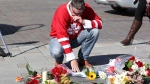 Richard Noble lays flowers on The Tragically Hip commemorative plaque in Kingston, Ont., on Wednesday, October 18, 2017. Gord Downie, the poetic lead singer of the Tragically Hip whose determined fight with brain cancer inspired a nation, has died at the age of 53. THE CANADIAN PRESS/Lars Hagberg