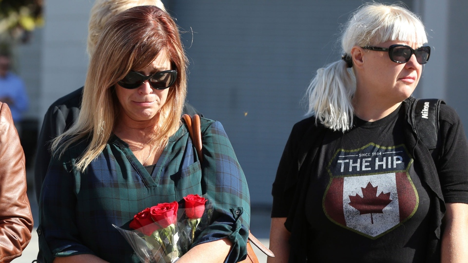 Melanie Wells looks at her flowers while waiting to sign a book of condolence for the late Gord Downie, lead singer of the Tragically Hip, in Kingston, Ont. on Wednesday Oct., 18, 2017.THE CANADIAN PRESS/Lars Hagberg