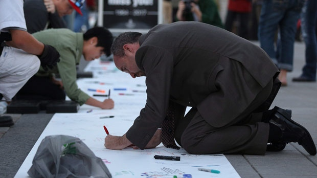 Kingston's Mayor Bryan Paterson writes messages for Gord Downie of the Tragically Hip on a banner in downtown Kingston, Ont., Wednesday Oct., 18, 2017. THE CANADIAN PRESS/Lars Hagberg