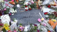 Flowers lay around a plaque for the Tragically Hip in downtown Kingston, Ont., Wednesday Oct., 18, 2017. THE CANADIAN PRESS/Lars Hagberg