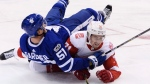 Toronto Maple Leafs defenceman Jake Gardiner (51) falls over Detroit Red Wings centre Dylan Larkin (71) during third period NHL hockey action in Toronto on Wednesday, October 18, 2017. THE CANADIAN PRESS/Nathan Denette