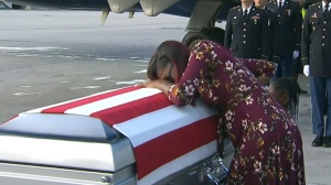 """In this Tuesday, Oct. 17, 2017, frame from video, Myeshia Johnson cries over the casket in Miami of her husband, Sgt. La David Johnson, who was killed in an ambush in Niger. President Donald Trump told the widow that her husband """"knew what he signed up for,"""" according to Rep. Frederica Wilson who said she heard part of the conversation on speakerphone. (WPLG via AP)"""