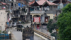 Philippine troops head back to the devastated village of Mapandi which has been cleared of Islamic State group-linked militants in Marawi city in southern Philippines Thursday, Oct. 19, 2017. Two days after President Rodrigo Duterte declared the liberation of Marawi city, the military announced the killing of more suspected militants in the continuing military offensive. (AP Photo/Bullit Marquez)