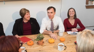 Minister of Finance Bill Morneau speaks with, from left to right, Alaina Lockhart, MP for Fundy Royal, and Angie Cummings, President of Sussex sleep clinic Inc., at Station 33 Cafe & Yoga in Hampton, N.B., on Wednesday, October 18, 2017. THE CANADIAN PRESS/Stephen MacGillivray