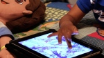 In this Friday, Oct. 21, 2011, file photo, a child plays with an iPad in his bedroom. (AP Photo/Gerald Herbert, File)