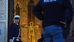 Police officers stand at the entrance of the Santa Croce Basilica where a 52-year-old tourist from Spain was killed by falling masonry, in Florence, Italy, Thursday, Oct. 18, 2017.. (Maurizio Degl'Innocenti/ANSA via AP)