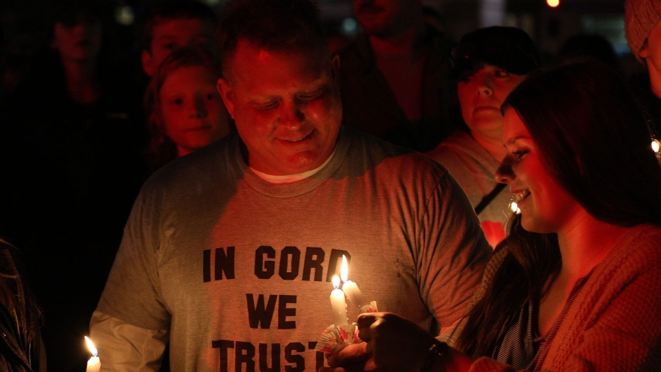 People stand with candles during a vigil for Gord Downie of the Tragically Hip in downtown Kingston, Ont., Wednesday Oct., 18, 2017. THE CANADIAN PRESS/Lars Hagberg