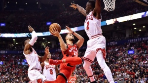 Toronto Raptors guard Fred VanVleet (23) shoots as he flies through the air as Chicago Bulls guard David Nwaba, left, and Bulls guard Jerian Grant (2) defend during first half NBA basketball action in Toronto on Thursday, October 19, 2017. THE CANADIAN PRESS/Frank Gunn