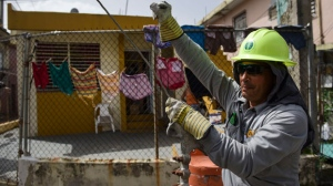 In this Thursday, Oct. 19, 2017 photo, Ezequiel Rivera works with the Electric Energy Authority to restore distribution lines damaged by Hurricane Maria in the Cantera community of San Juan, Puerto Rico. The office of Gov. Ricardo Rossello said Thursday, Oct. 19 that about 20 percent of the island has service and he has pledged to get that to 95 percent by Dec. 31. (AP Photo/Carlos Giusti)