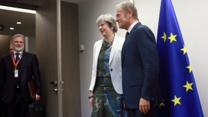 British Prime Minister Theresa May, center, meets with European Council President Donald Tusk, right, during an EU summit in Brussels on Friday, Oct. 20, 2017. European Union leaders gathered Friday to weigh progress in negotiations on Britain's departure from their club as they look for new ways to speed up the painfully slow moving process. (Olivier Hoslet, Pool Photo via AP)