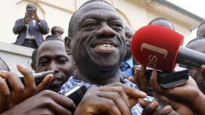 Former Presidential Candidate Kizza Besigye, center, is interviewed by journalists after being released on bail at the High Court in Kampala, Uganda, Tuesday July 12, 2016. Besigye was freed Tuesday after spending two months in jail over treason charges after he claimed an election victory over the country's long-time president. (AP Photo Stephen Wandera)