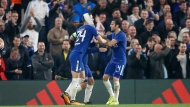 Chelsea's Eden Hazard, covered by his teammates, celebrates after scoring during the Champions League group C soccer match between Chelsea and Roma at Stamford Bridge stadium in London, Wednesday, Oct. 18, 2017. (AP Photo/Frank Augstein)