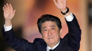 In this Oct. 18, 2017 photo, Japan's Prime Minister and President of the ruling Liberal Democratic Party Shinzo Abe waves to the crowd in support for his party's candidate during an election campaign for the upcoming lower house election in Tokyo. Media polls indicate Abe's ruling coalition will handily win a general election Sunday, Oct. 22 possibly even retaining its two-thirds majority in the more powerful lower house of parliament (AP Photo/Shizuo Kambayashi)