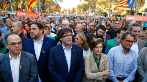 Catalan President Carles Puigdemont, centre, takes part at a march with deputy president Oriol Junqueras, 2nd left, Carme Forcadell, speaker of the house in the Catalan parliament, 4th left and former Catalan President Artur Mas, right,to protest against the National Court's decision to imprison civil society leaders, in Barcelona, Spain, Saturday, Oct. 21, 2017. The Spanish government moved decisively Saturday to use a previously untapped constitutional power so it can take control of Catalonia and derail the independence movement led by separatist politicians in the prosperous industrial region. AP Photo/Manu Fernandez)