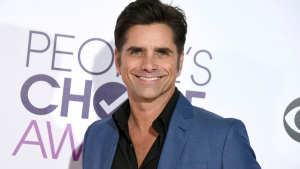 In this Jan. 18, 2017 file photo, John Stamos arrives at the People's Choice Awards at the Microsoft Theater in Los Angeles. Stamos announced his engagement to actress Caitlin McHugh on social media Oct. 22, 2017. (Photo by Jordan Strauss/Invision/AP, File)