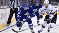 Toronto Maple Leafs centre Mitchell Marner (16) carries the puck into the offensive zone as Los Angeles Kings centre Nick Shore (21) defends during second period NHL hockey action in Toronto on Monday, October 23, 2017. THE CANADIAN PRESS/Nathan Denette