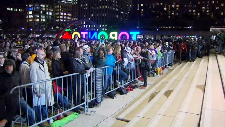 Fans are seen at Nathan Phillips Square for a tribute to the late Gord Downie.
