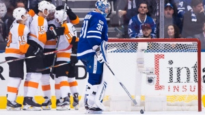 Toronto Maple Leafs goalie Frederik Andersen (31) pushes the puck out of the net as Philadelphia Flyers players celebrate their goal during second period NHL hockey action in Toronto on Saturday, October 28, 2017. THE CANADIAN PRESS/Nathan Denette