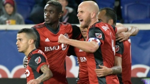 Toronto FC midfielder Michael Bradley (4) celebrates a goal by Victor Vazquez, rear right, during the first half of an MLS Eastern Conference semifinal soccer match against the New York Red Bulls Monday, Oct. 30, 2017, in Harrison, N.J. (AP Photo/Bill Kostroun)